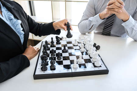 Businessman and businesswoman playing chess and thinking about strategy crash overthrow the opposite team and development analysis for win and successful.