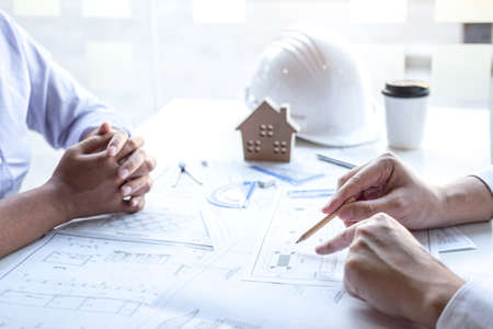 Team of construction engineering or architect partner discuss a blueprint while checking information on drawing and sketching meeting for architectural project with engineering equipment tool.