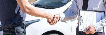Insurance agent shaking hands client after examine the damage of the car after accident on report claim form process. Archivio Fotografico