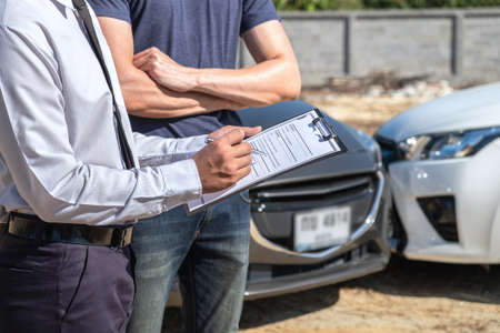 Insurance agent examine the damage of the car after accident on report claim form process.