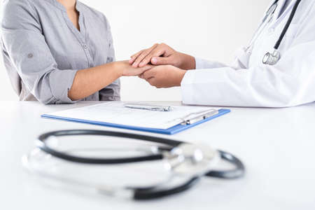 Image of doctor holding patient's hand to encourage, talking with patient cheering and support, healthcare and medical assistant.