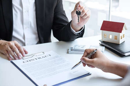 Estate agent giving house keys to client after signing agreement contract real estate with approved mortgage application form, concerning mortgage loan offer for and house insurance. Imagens