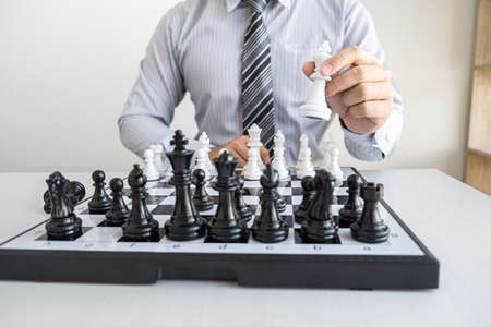 Businessman playing chess and thinking strategy about crash overthrow the opposite team and development analysis for win and successful.