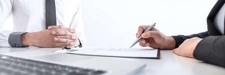 Employer or recruiter holding reading a resume during about colloquy his profile of candidate, employer in suit is conducting a job interview, manager resource employment and recruitment concept. Фото со стока