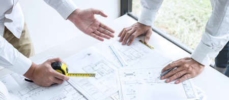 Construction engineering or architect discussing a blueprint and building model while checking information on sketching meeting for architectural project in work site.