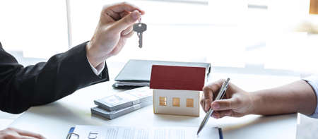 Estate agent giving house keys to client after signing agreement contract real estate with approved mortgage application form, concerning mortgage loan offer for and house insurance. Фото со стока