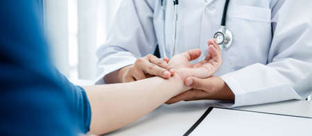 The doctor hold the patient on the wrist to take the pulse heart rate, the doctor work at the clinic explain about treatment, health care and writing a prescription medicine to patient