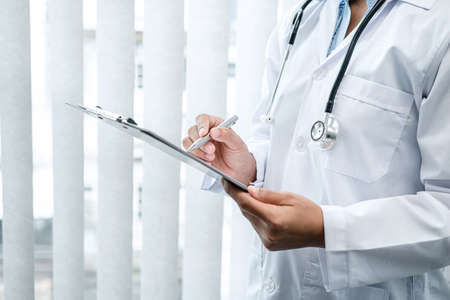 The doctor is standing and reading medical report inside his office, the doctor is reading the patient's symptoms and analyze treatment, Healthcare and medicine used to treat the patient Фото со стока