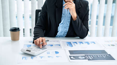 Business woman are the numeric data from the chart using a calculator, investment chart using the calculator on the desk in her office working by reviewing