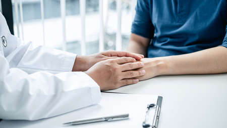 Doctor holding hands on patient about bad news at consulting room, to encourage, supporting, fight for disease and advice treatment and medicine at his hospital office. Фото со стока