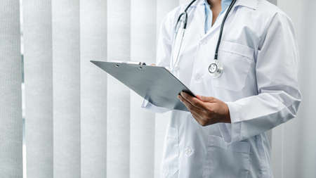 The doctor is standing and reading medical report inside his office, the doctor is reading the patient's symptoms and analyze treatment, Health care and medicine used to treat the patient