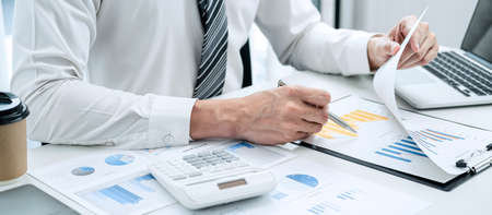Business man hold pen to check investment data with a calculator, the chart contains costs expenses profits use in the business