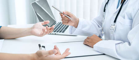 Doctor hold pen and patient discussing something in medical clinic, doctor talk about medicine ,health care concept and writing a prescription Фото со стока
