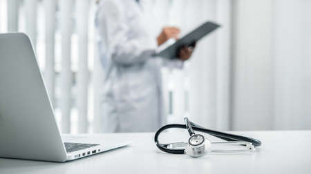 Doctor is standing and reading report and Stethoscope is on the table, doctor is reading symptoms of the patient and analyze treatment, health care and medicine at his hospital office Фото со стока