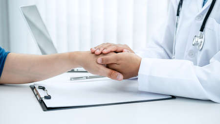 Doctor holding touching hand after reading bad result at clinic, Having with love, support, care, help and good healthy concept to patient Reklamní fotografie