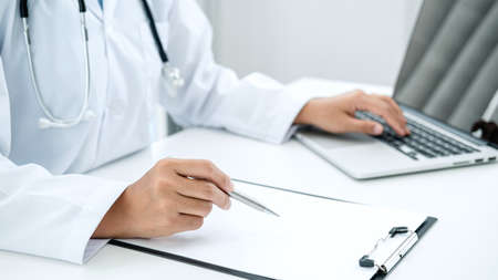 Doctor hold pen to record patient data on clipboard and computer, Doctor writing a prescription and working in the hospital