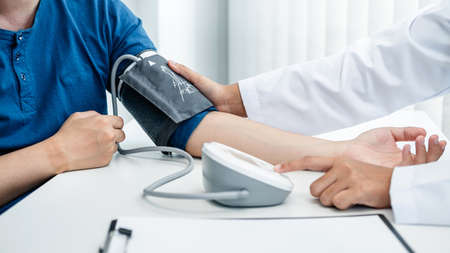 Doctor is checking the patient blood pressure in his hospital office, and doctor is pressing a button, an instrument used for measuring blood pressure on the table