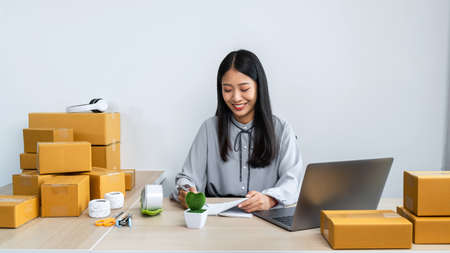 Online shopping, Young business woman entrepreneur taking order from client and checking order on laptop to confirm before sending by post office