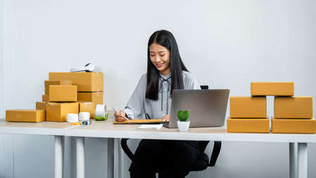 Young business woman entrepreneur writing address on cardboard box and receive order client, courier preparing packing product to parcel box and sending on purchase delivery online at home office