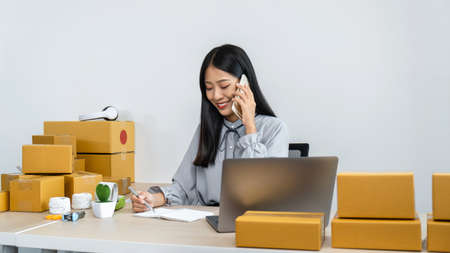 Young business woman entrepreneur receive order client with smartphone and writing address on notebook, courier preparing packing product to parcel box to sending delivery online Reklamní fotografie