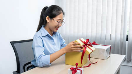 Young asian woman opening a gift box with red ribbon and looking inside box with smiling to enjoy celebration on christmas festival at office workspace