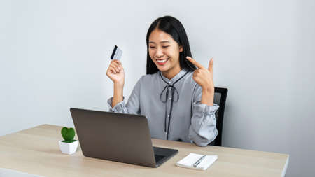 Young asian woman using laptop for online shopping and holding credit card entering information for purchase order to online payment