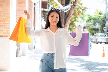 Asian woman shopaholic smiling with many colorful shopping bags and holding credit card for payment after make purchase in shopping mall