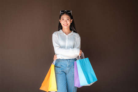 Portrait of asian shopaholic woman smiling and wearing sunglasses headband with many colorful shopping bags in both hands after heavy shopping isolated over brown background Reklamní fotografie