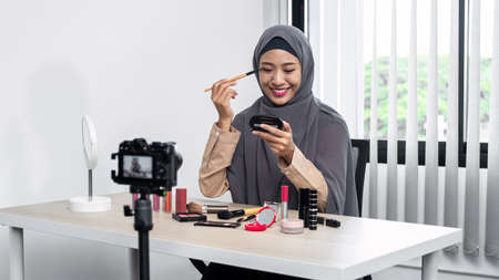 Asian muslim woman beauty blogger tutorial by eye shadow makeup on her eyes and making videos to review cosmetic products for her vlog and blogger to share on website or social media Reklamní fotografie
