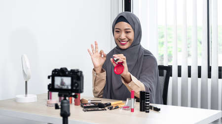 Asian muslim woman beauty blogger review blush on showing on her hand and recommend to use this brand of blush on while recording video for her vlog and blogger to share on website or social media