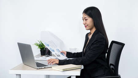 Young secretary woman holding paper document to typing email to her boss and clients while sitting at the table in office