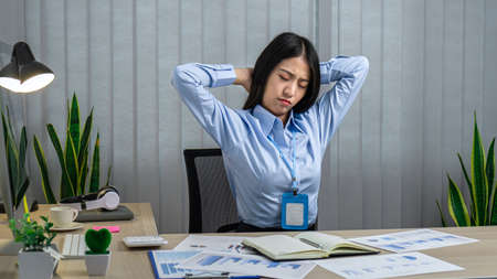 Asian woman office worker close eyes and raising hands to rest at back of head while sitting to relaxing for break time after work hard in office
