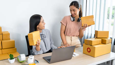 Two young business woman entrepreneur are talking and holding parcel box, couriers are checking order on laptop and preparing packing product sending home delivery to client Reklamní fotografie