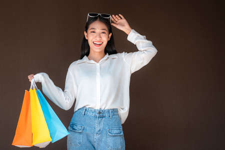 Portrait of asian shopaholic woman holding sunglasses headband with many colorful shopping bags after heavy shopping isolated over brown background Reklamní fotografie