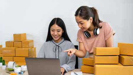 Two young business woman entrepreneur are talking with client on laptop and confirm order form client, couriers are preparing many parcel box for packing product sending home delivery