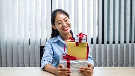 Young asian woman smiling and holding with many gift box at office workspace, she is preparing presents for celebration on christmas festival Reklamní fotografie