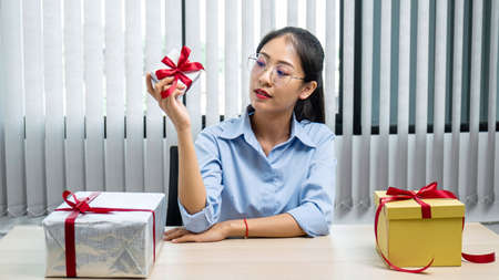 Young asian woman holding a small silver gift box to preparing celebration on christmas festival, she wrap many presents at office workspace