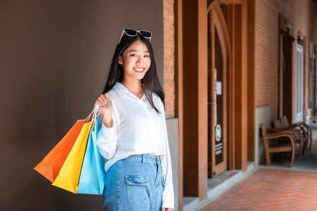 Portrait of asian shopaholic woman smiling and wearing sunglasses headband with many colorful shopping bags after make purchase and payment heavy shopping in shopping mall