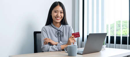 Young asian woman smiling and holding credit card while using laptop for online shopping to buy product and entering information for purchase order to online payment