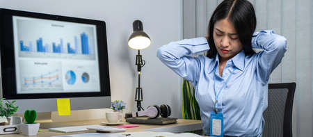 Asian woman office worker close eyes and raising hands to rest at back of head while sitting to relaxing for break time after work hard in office. Reklamní fotografie
