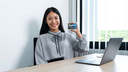 Young asian woman smiling and presenting credit card in her hands to showing confidence for making payment of online shopping
