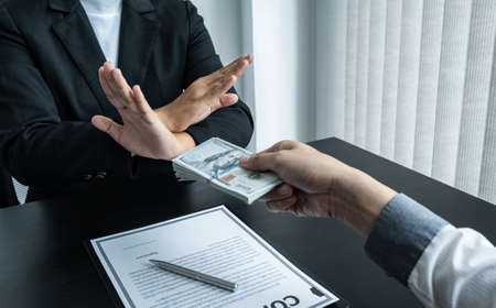 Business woman refusing and don't receive money banknote in envelope offer from business people to accept agreement contract of investment deal. Reklamní fotografie