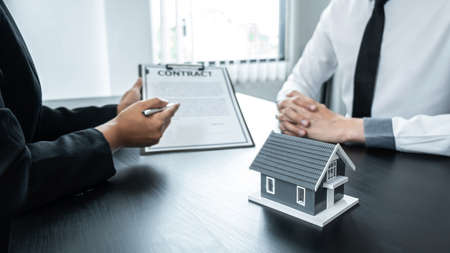 Estate agent broker presentating to client decision signing agreement contract real estate with approved mortgage application, buying mortgage loan offer for and house insurance. Reklamní fotografie