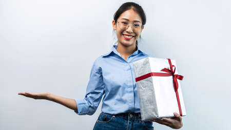 Portrait of happy asian girl holding present box while standing, and looking at the camera, the girl holding silver gift box with red ribbon in holiday celebration concept