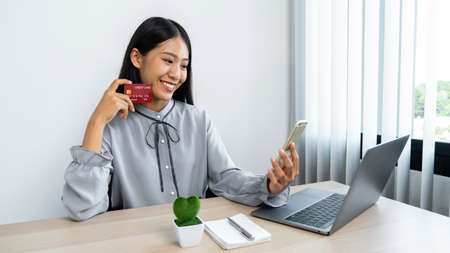 Young asian woman smiling and showing credit card in her hands for online shopping while looking on smartphone to using mobile banking and entering security authorization code