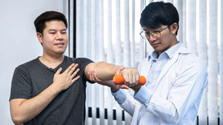 Young asian physiotherapist helping male patient stretching arm during exercise correct with dumbbell in hand during training hand to rehabilitation therapies in clinic