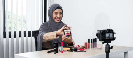 Asian muslim woman beauty blogger looking at the camera to review eye shadow showing on her hand and recording video for her vlog and blogger to share on website or social media
