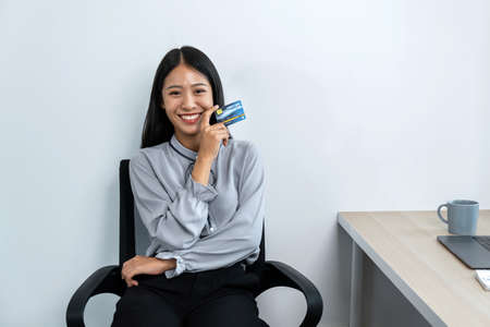 Portrait of young asian woman smiling and holding credit card in her hands to showing trust and confidence for making payment of online shopping Reklamní fotografie