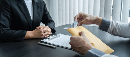 Dishonest cheating in illegal money, Businessman giving bribe money the form of dollar bills to while give success the deal to contract agreement, Bribery and corruption concept. Reklamní fotografie