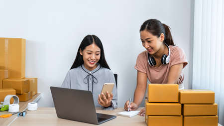 Two young business woman entrepreneur are checking order together on laptop and smiling while talking with client using smartphone, couriers are preparing packing product to parcel box home delivery Reklamní fotografie